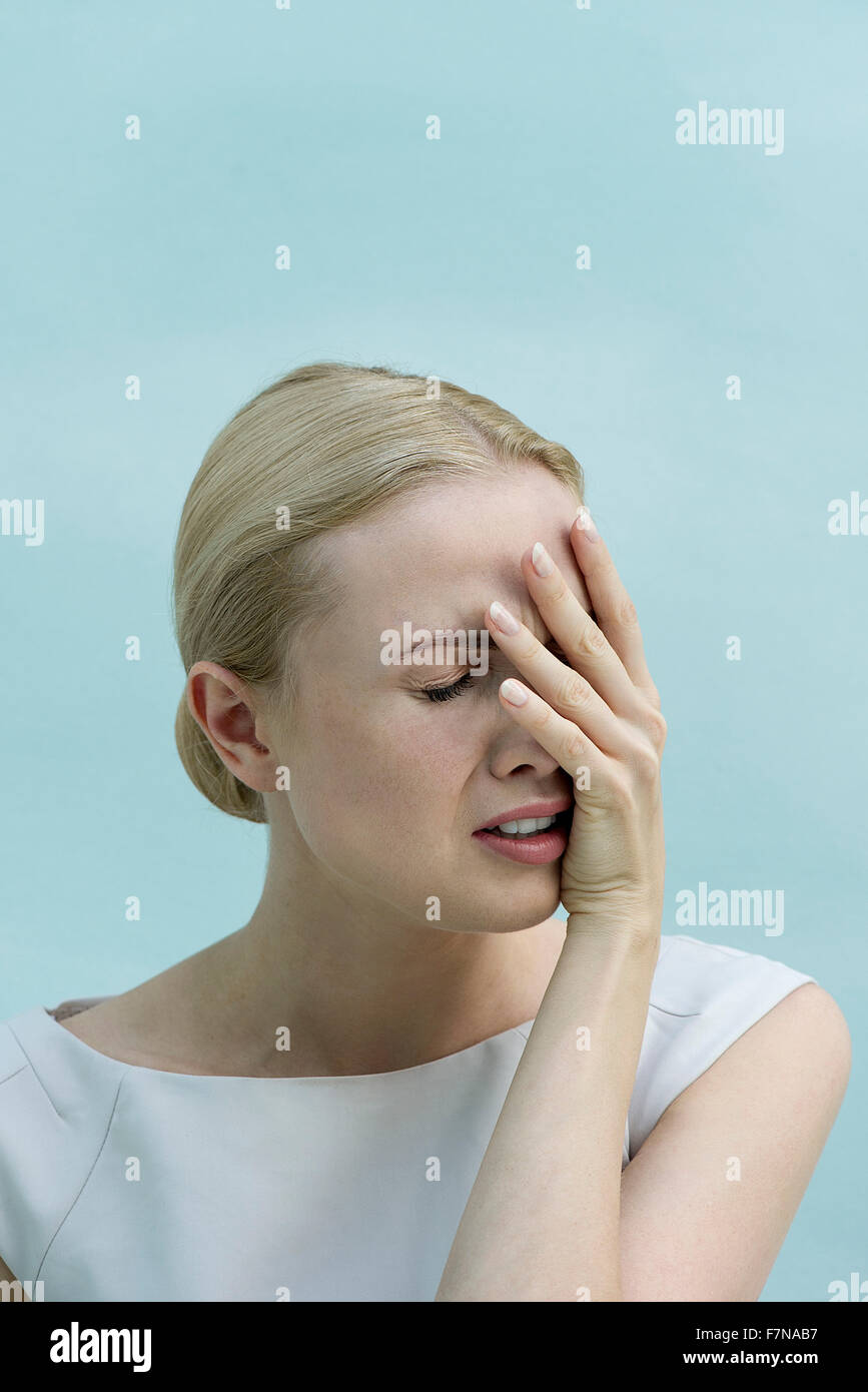 Woman covering face with hand and grimacing - Stock Image