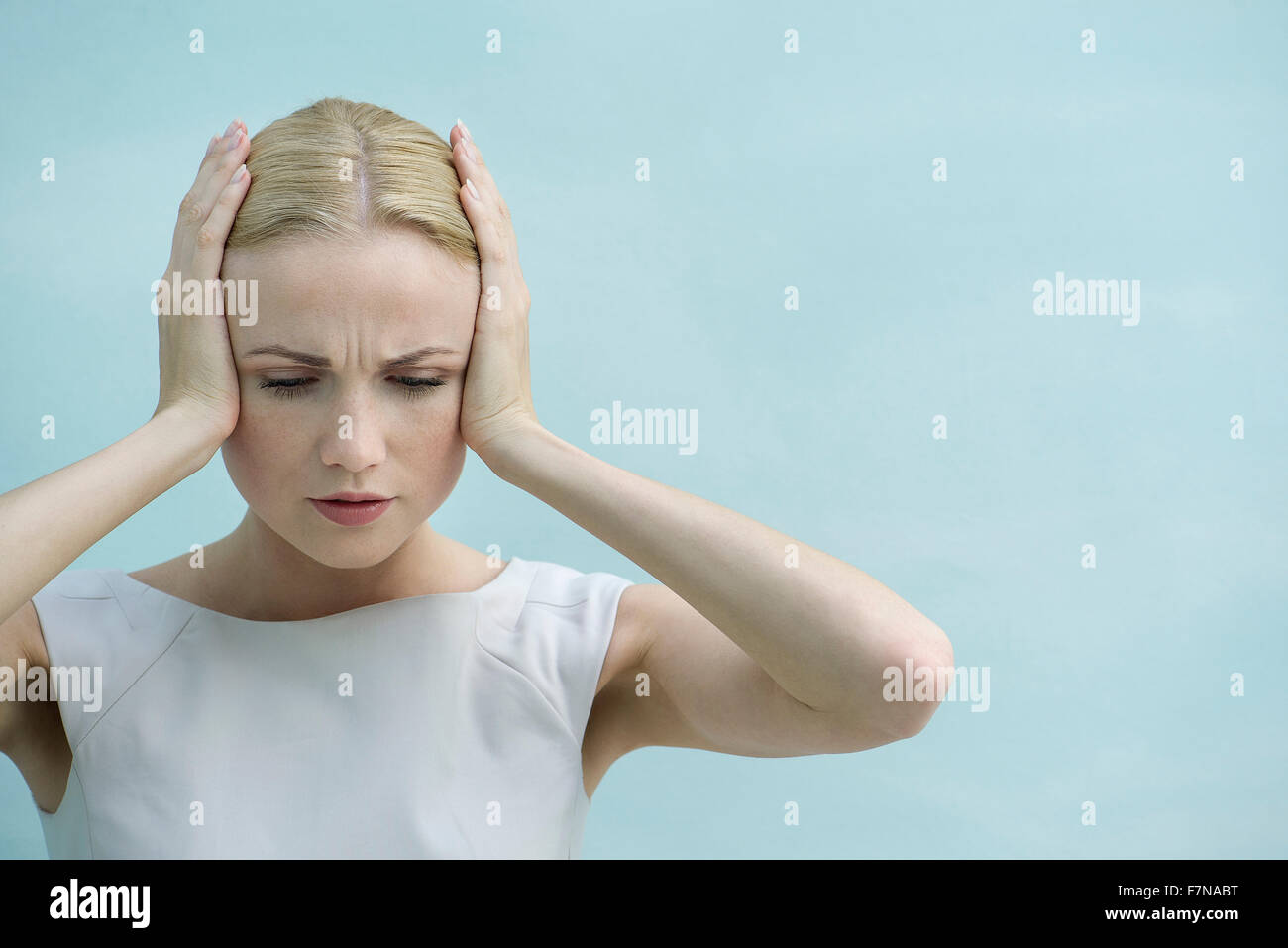 Woman holding hands over ears, looking down with furrowed brow Stock Photo