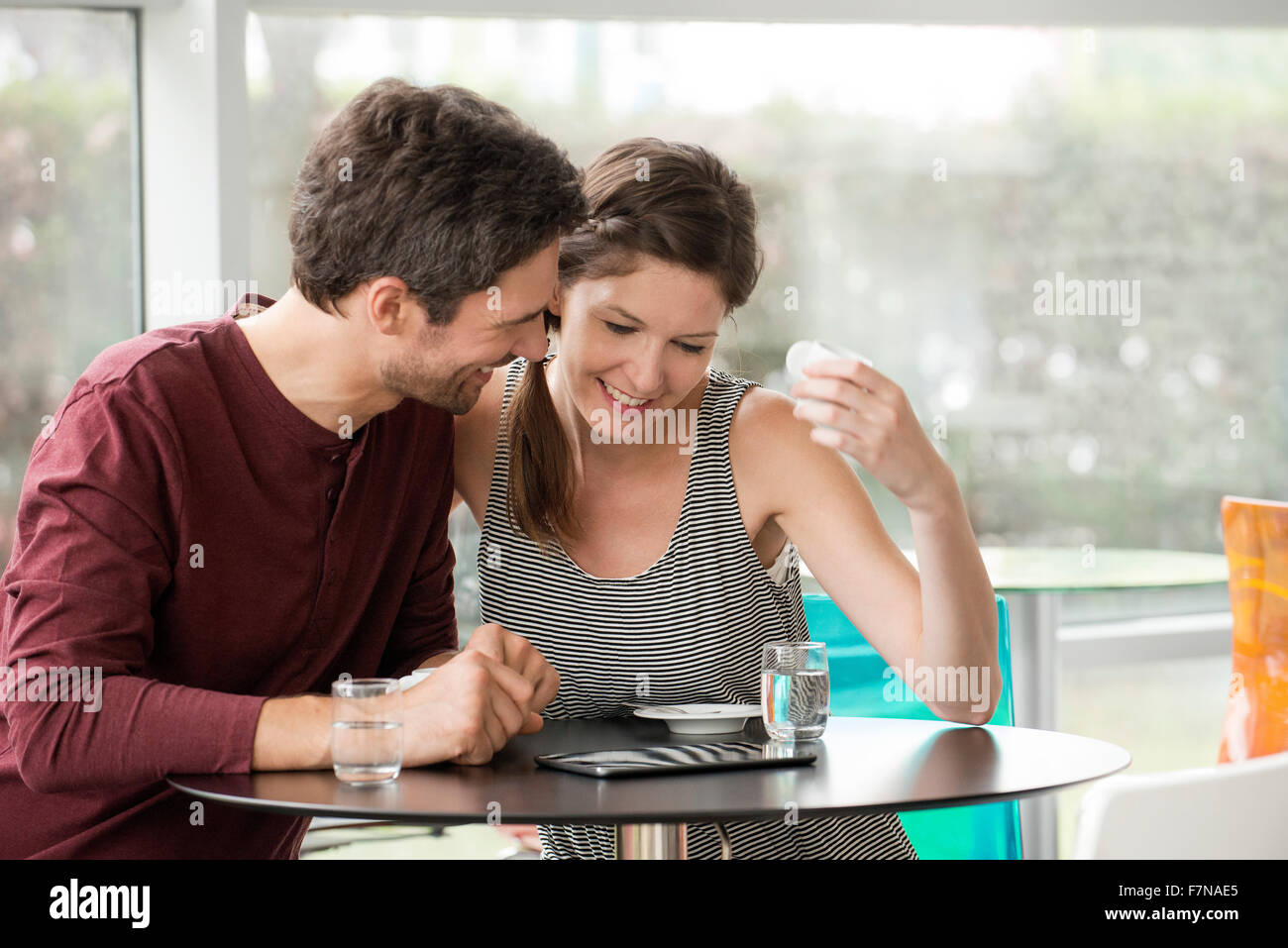 Couple in cafe watching video streaming on digital tablet - Stock Image
