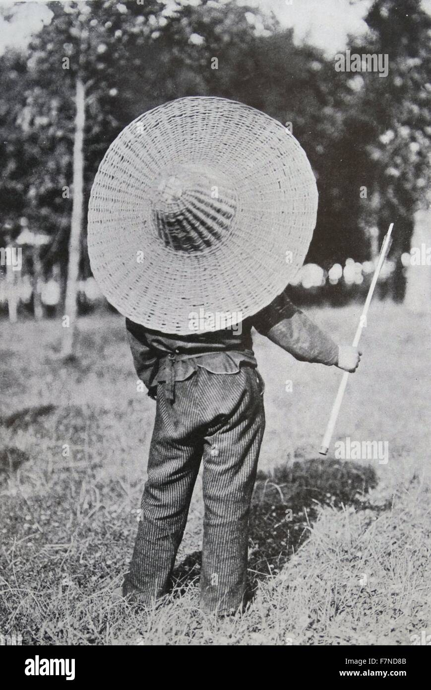 'arrow-proof' attendant.  A boy attendant who has to run out into the open to collect fallen arrows at a - Stock Image