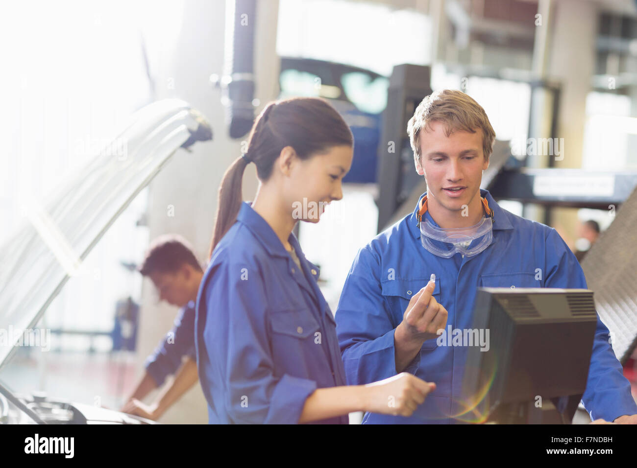 Mechanics discussing part at computer in auto repair shop - Stock Image
