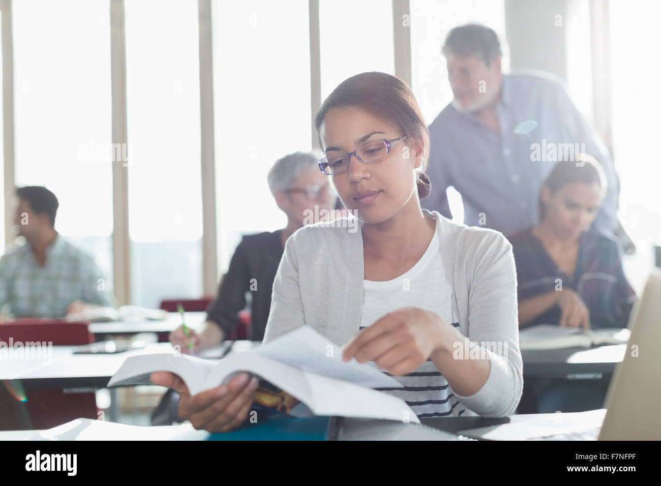 Student reading textbook in adult education classroom - Stock Image