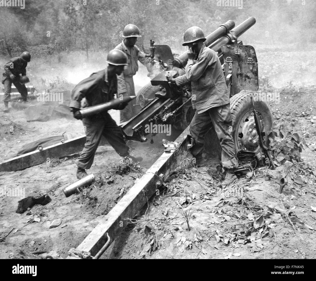 US Army artillery crew firing a 105 millimetre howitzer, against North Korean positions during the Korean War 1950 - Stock Image