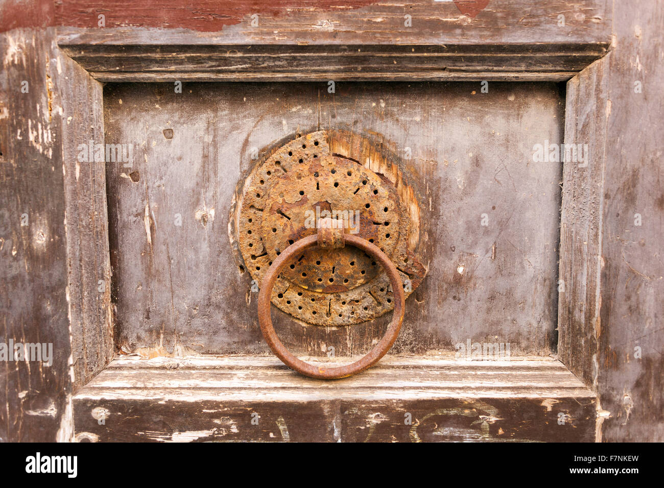 Old door knocker on rustical wooden door. - Stock Image