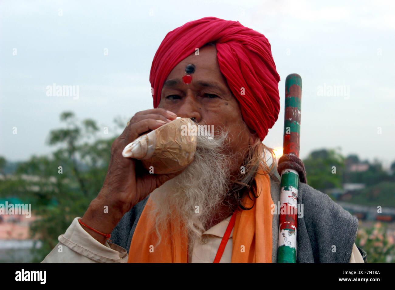 Sadhu blowing conch shell Kumbh Mela, Nasik, Maharashtra, India - Stock Image