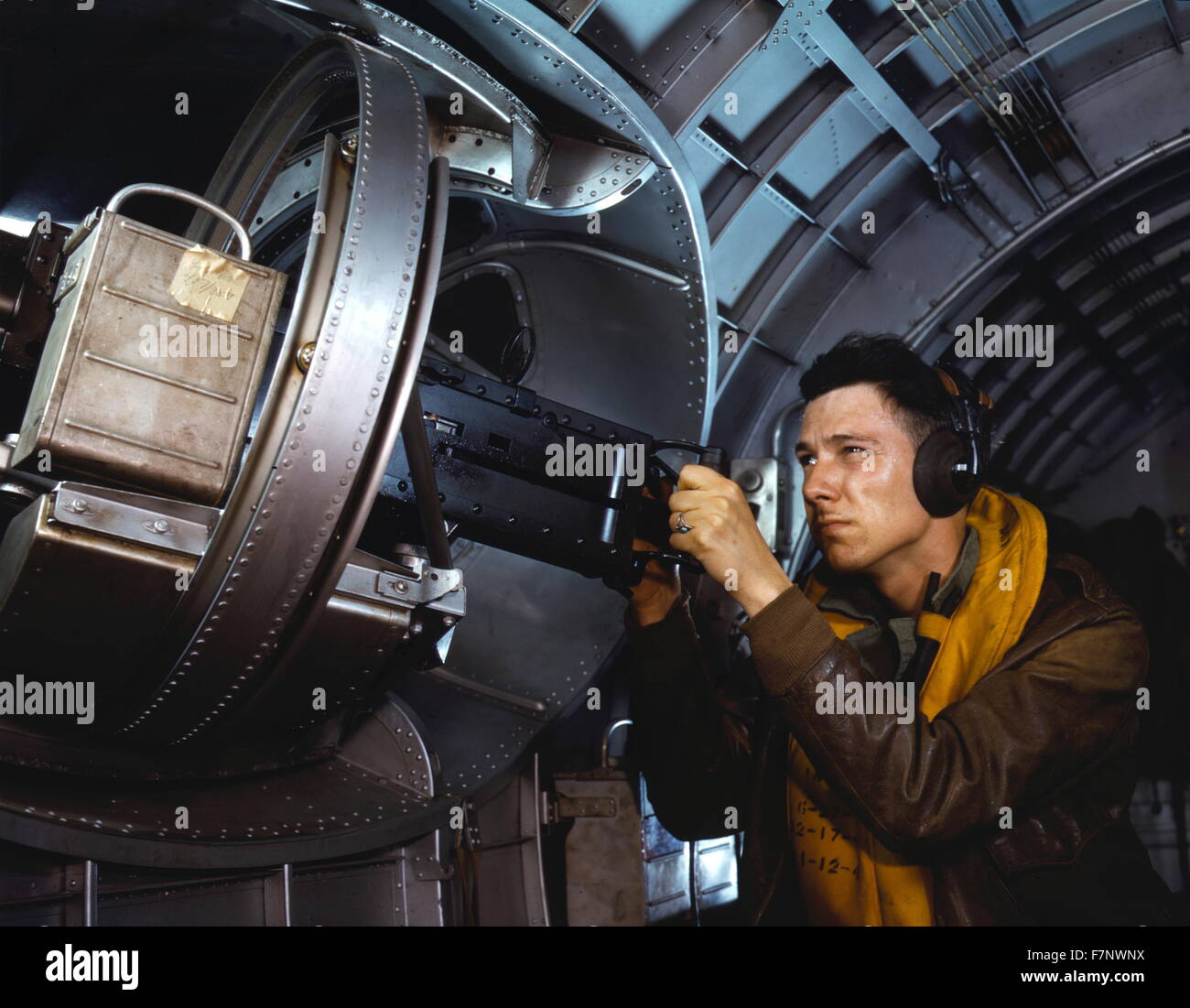American airman using a a side machine gun of a B-17 Flying Fortress bomber, May 1942. World war two - Stock Image