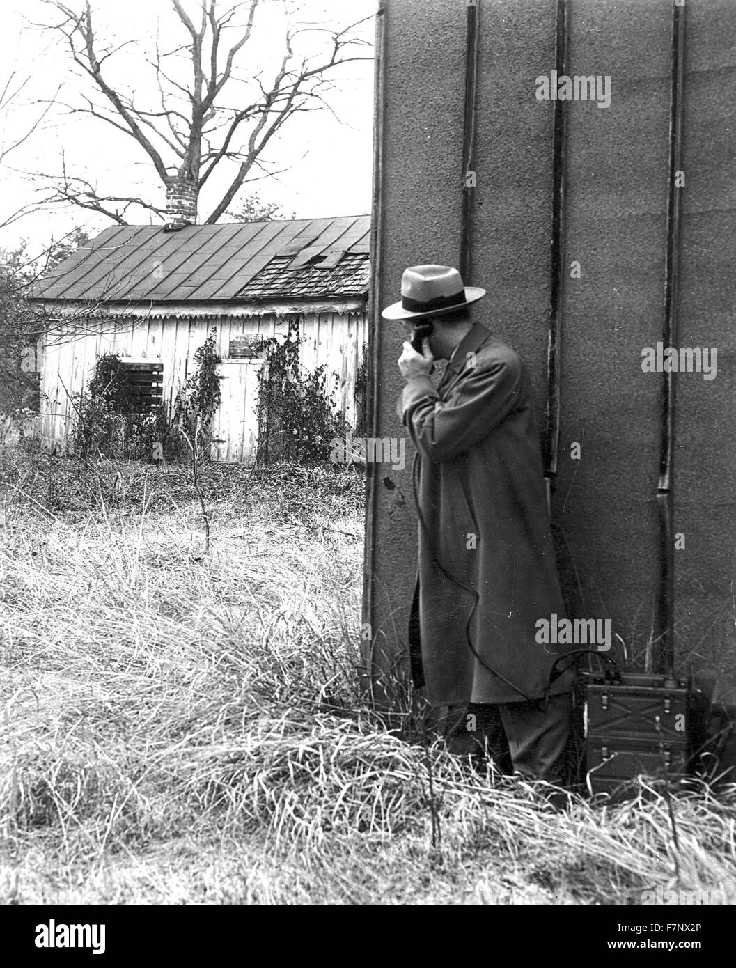 1930's FBI (federal Beureau of Investigation) officer (Agent), uses a portable phone during an operation - Stock Image