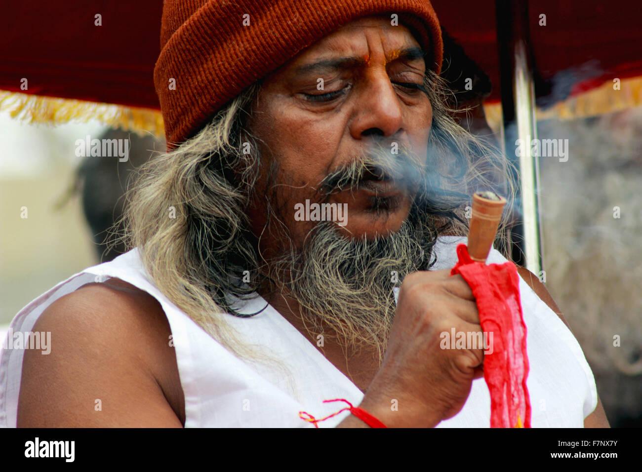 Sadhu smoking chillum Kumbh Mela, Nasik, Maharashtra, India Stock Photo