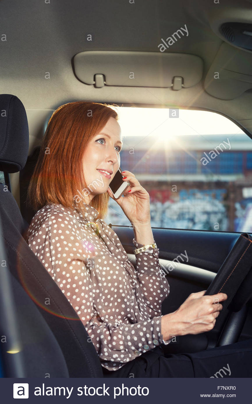Redheaded businesswoman sitting in her car telephoning with smartphone - Stock Image