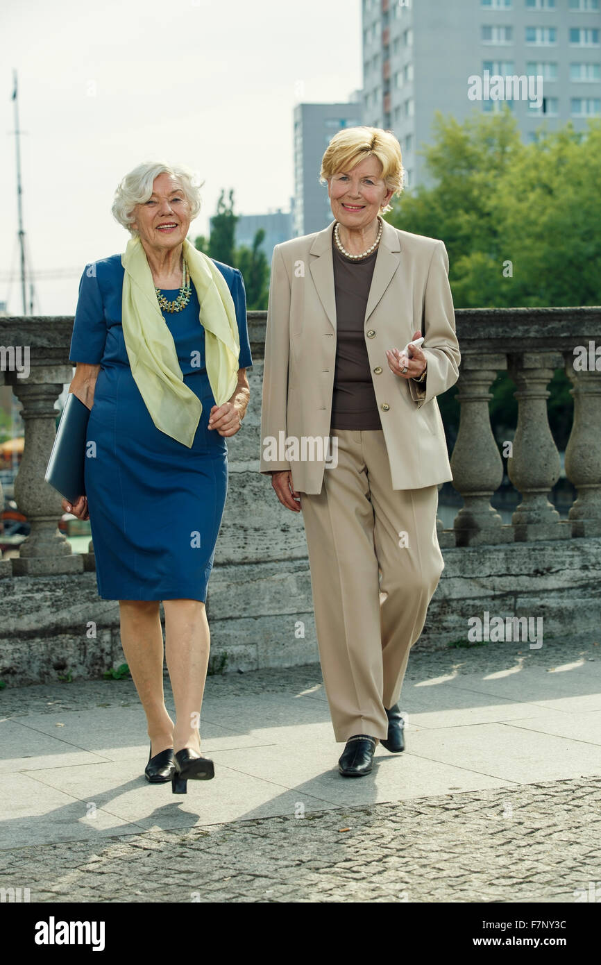 Germany, Berlin, portrait of two smiling senior businesswomen with laptop and smartphone Stock Photo