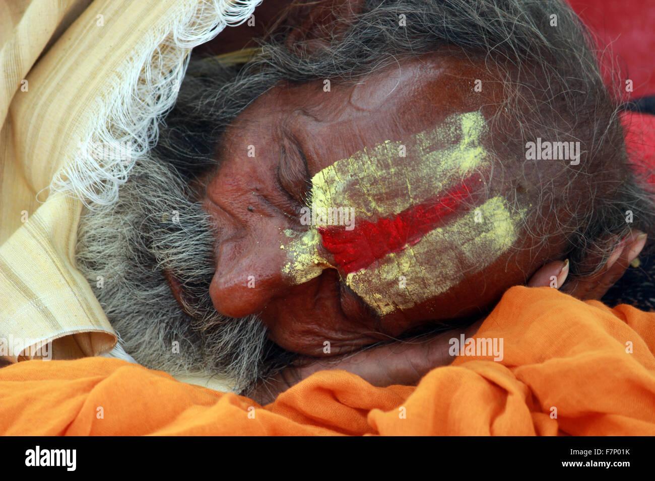 Sadhu with painted forehead sleeping Kumbh Mela, Nasik, Maharashtra, India - Stock Image