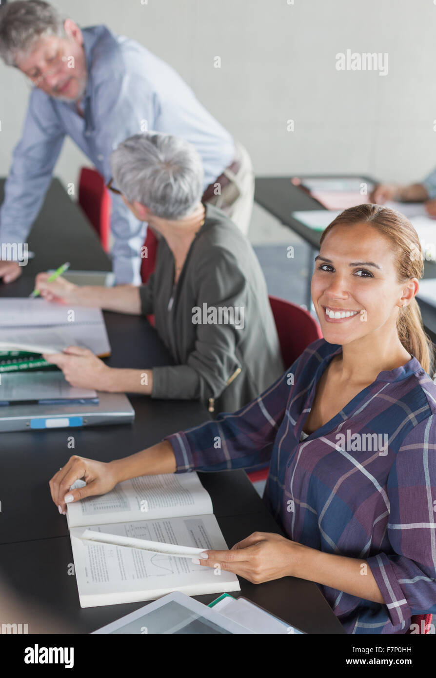 Portrait smiling student with textbook in adult education classroom - Stock Image