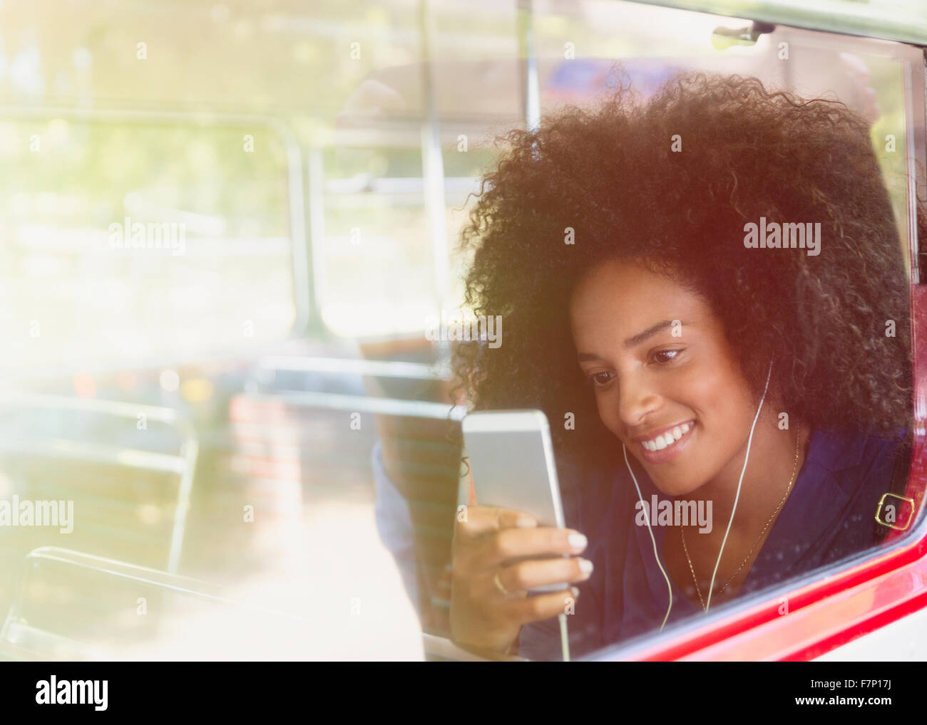 Smiling woman with afro listening to music with headphones and mp3 player on bus - Stock Image