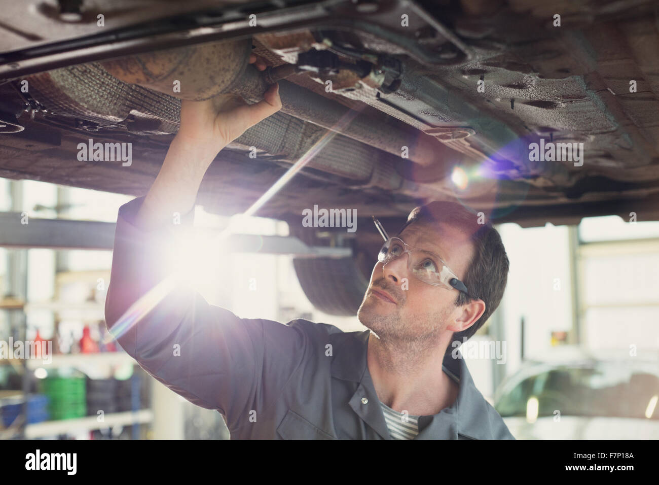 Mechanic working under car in auto repair shop - Stock Image
