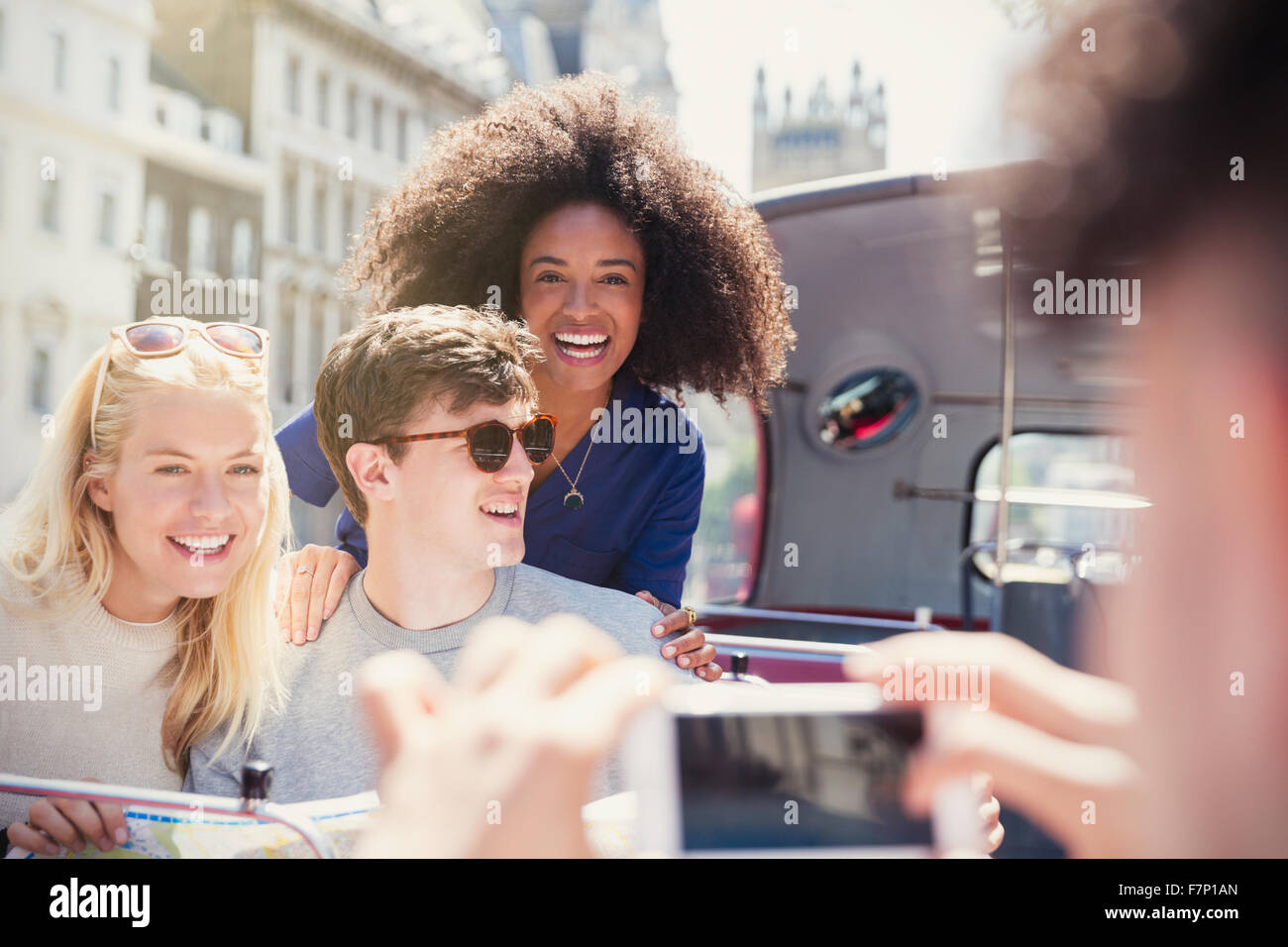 Enthusiastic friends being photographed on double-decker bus - Stock Image