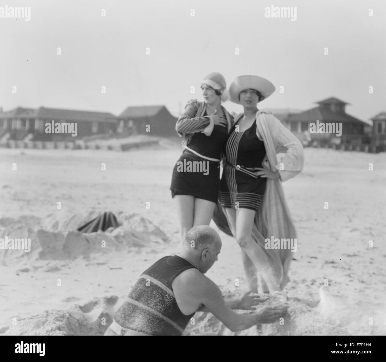 Unidentified man building sand castle and two women, Long Beach, New York 1910 by Arnold Genthe 1869-1942, photographer - Stock Image