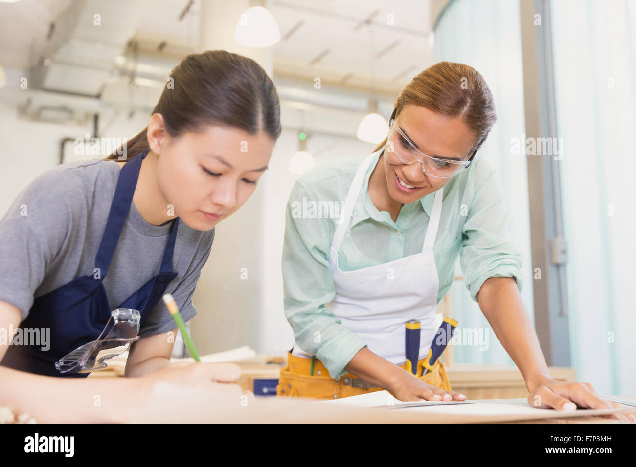 Female carpenters drafting plans in workshop - Stock Image