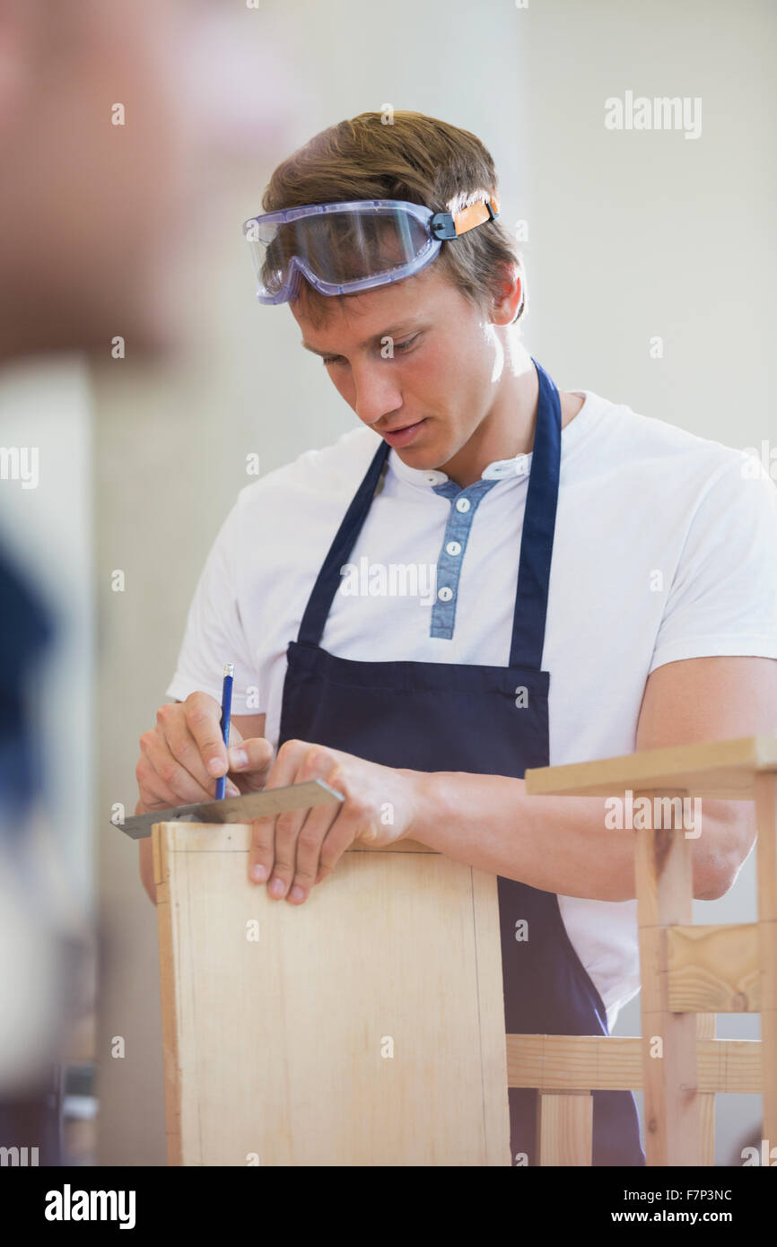 Carpenter measuring wood in workshop - Stock Image