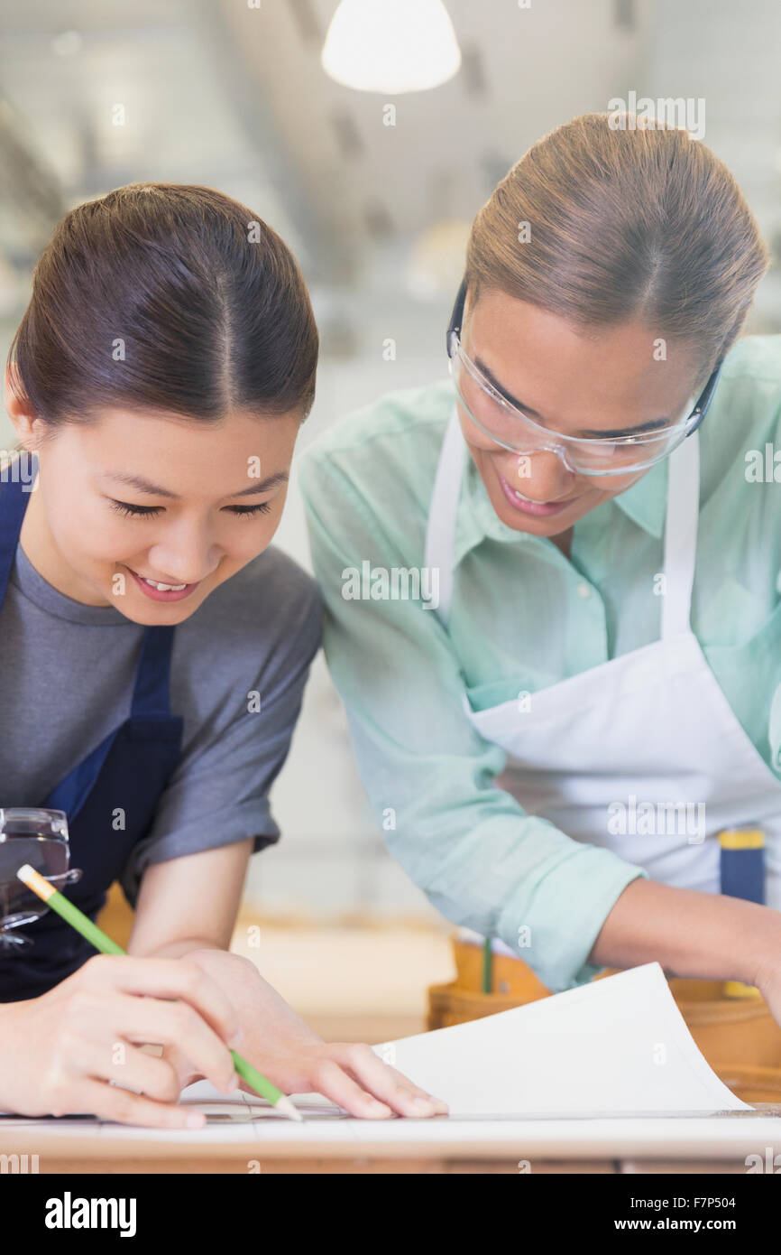 Female carpenters drafting blueprints in workshop - Stock Image