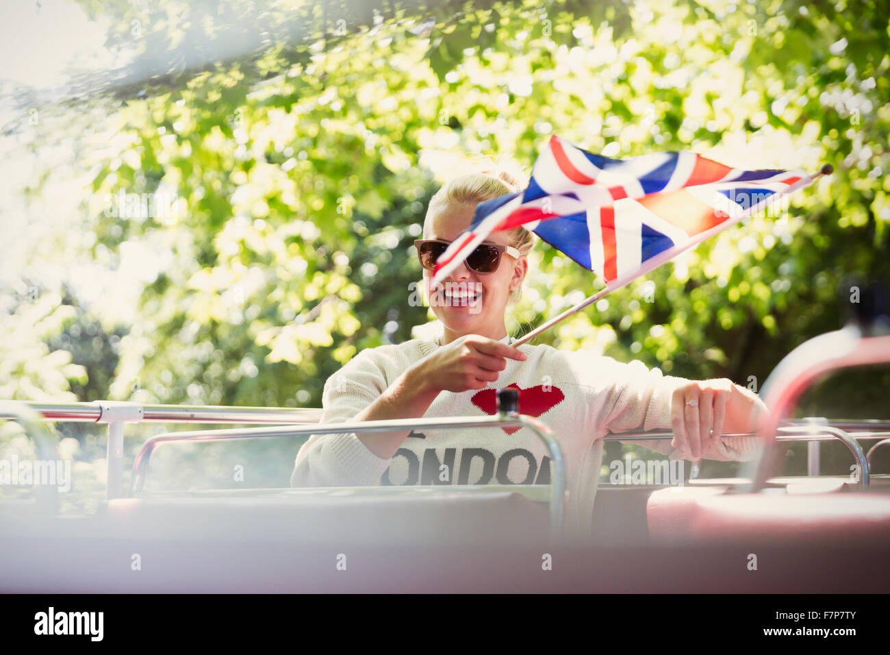 Smiling woman waving British flag on double-decker bus - Stock Image