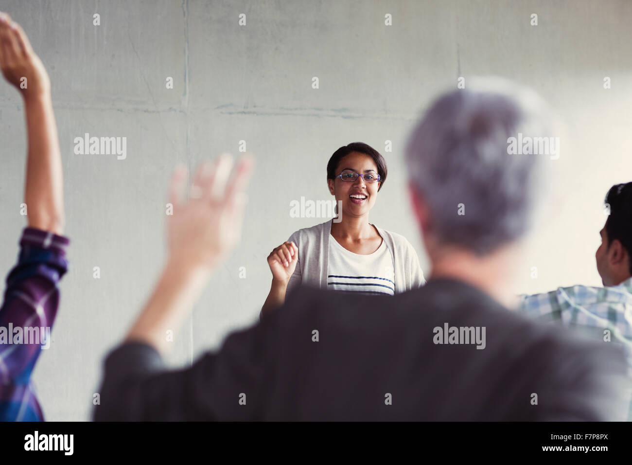 Teacher calling on students with hands raised in adult education classroom - Stock Image