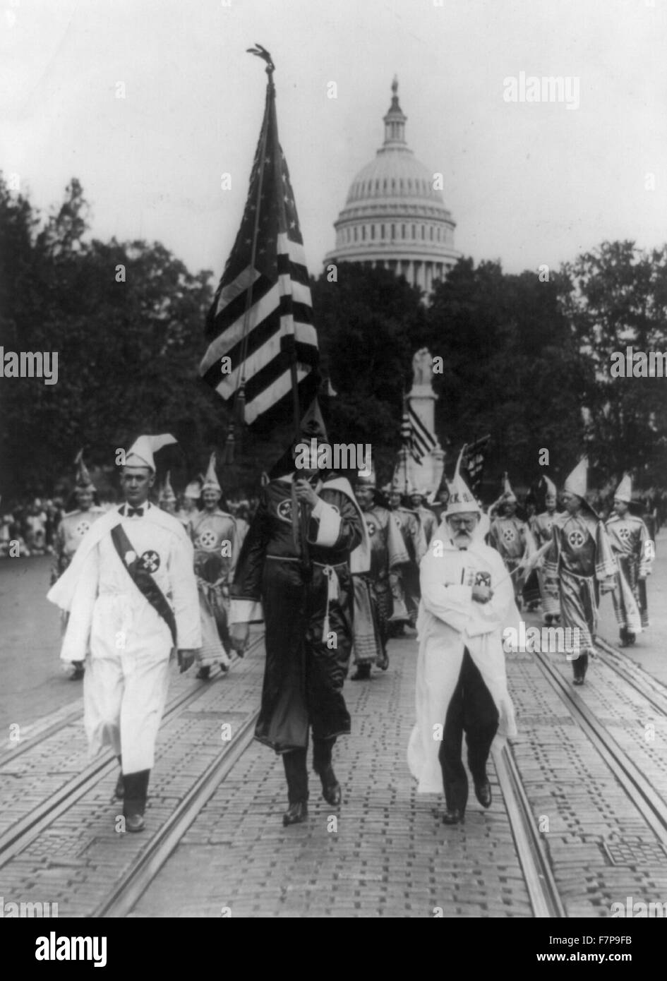 Photographic print shows a group parading on the street in front of the dome of the U.S. Capitol. In the background, - Stock Image