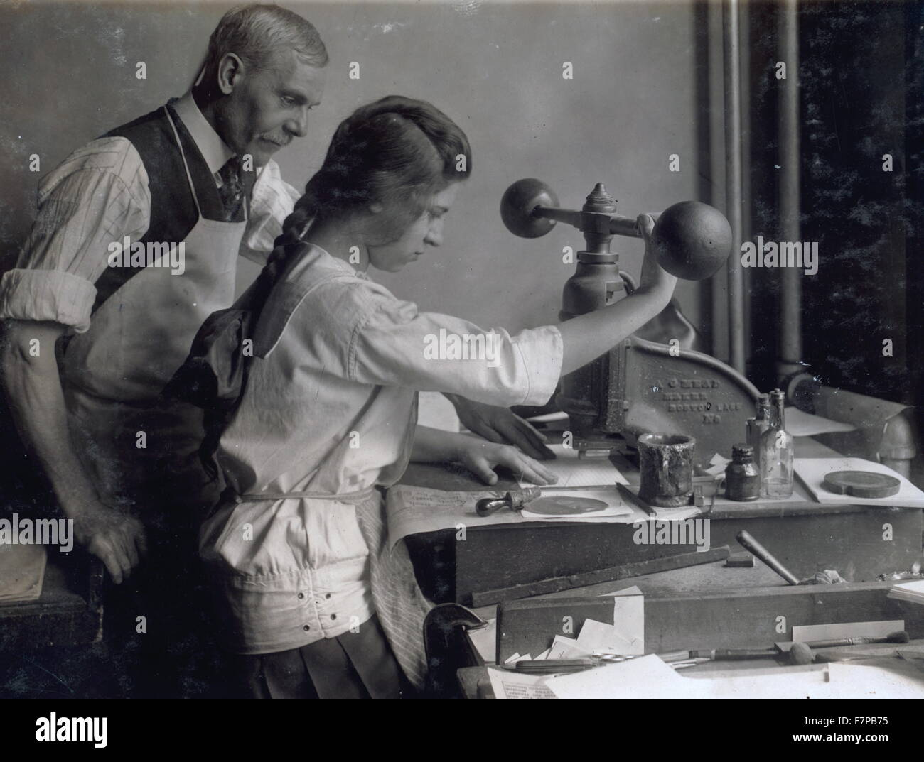 Photographic print of a 15 year old girl at embossing machine in the embossing shop of Harry C. Taylor, 61 Court - Stock Image