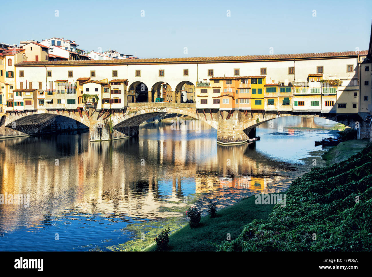Beautiful Ponte Vecchio is mirroring in the river Arno, Florence, Tuscany, Italy. Travel destination. Vibrant colors. - Stock Image
