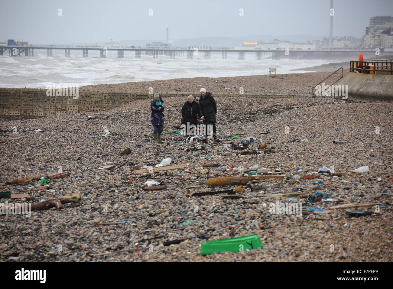 Three women walk amongst litter washed ashore on Brighton Beach 2 December 2015 after high winds and seas continue - Stock Image