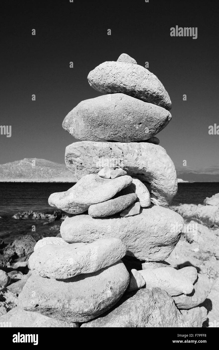 A tower of stones on Ftenagia beach at Emborio on the Greek island of Halki. - Stock Image