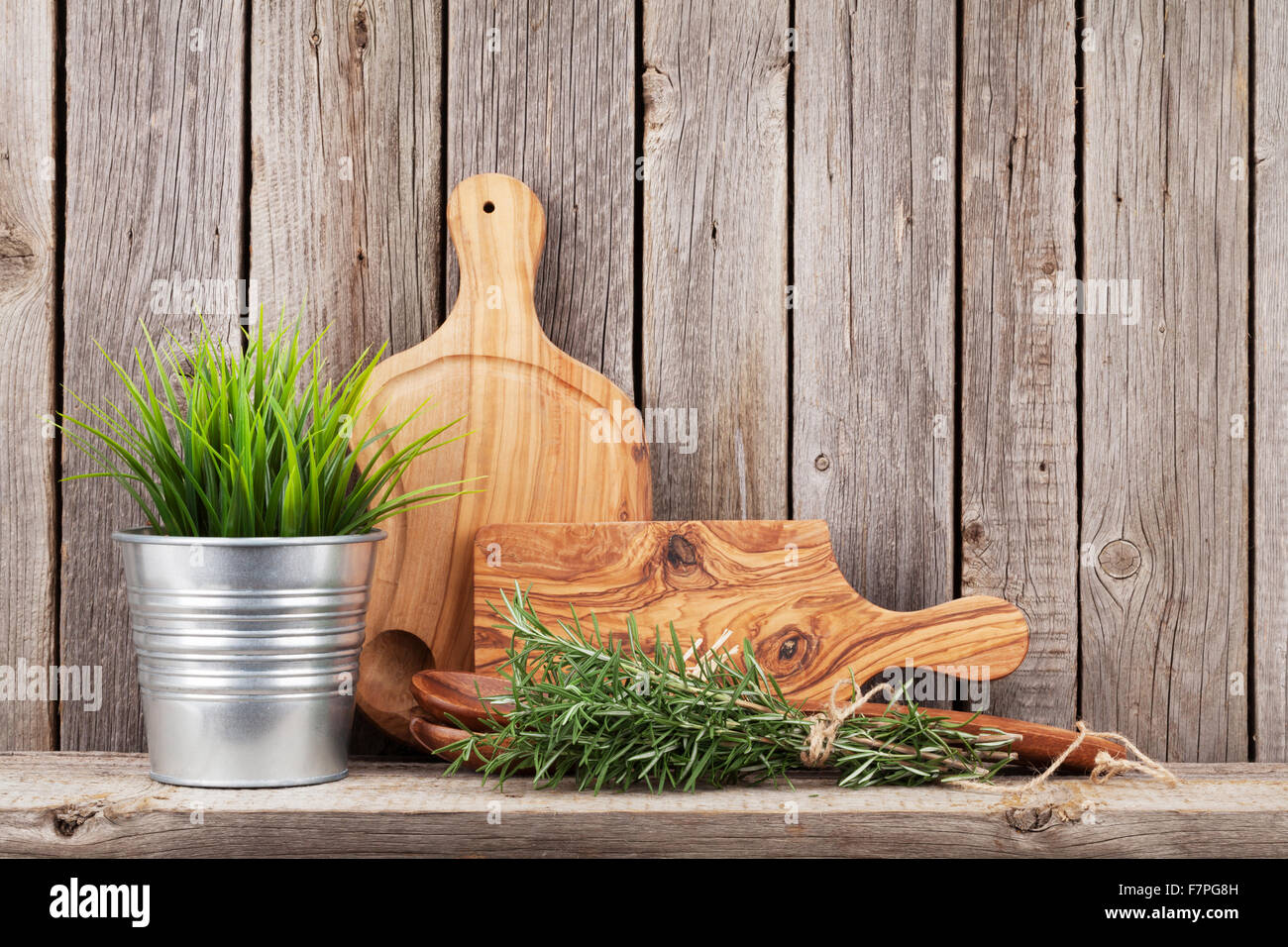 Cooking wood utensils and herbs on shelf in front of wooden wall with copy space - Stock Image