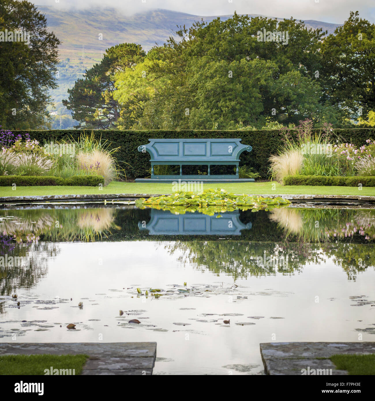 A bench reflected in the still water of a lily pond, on the Lily Terrace at Bodnant Garden, Conwy, Wales, in October. - Stock Image