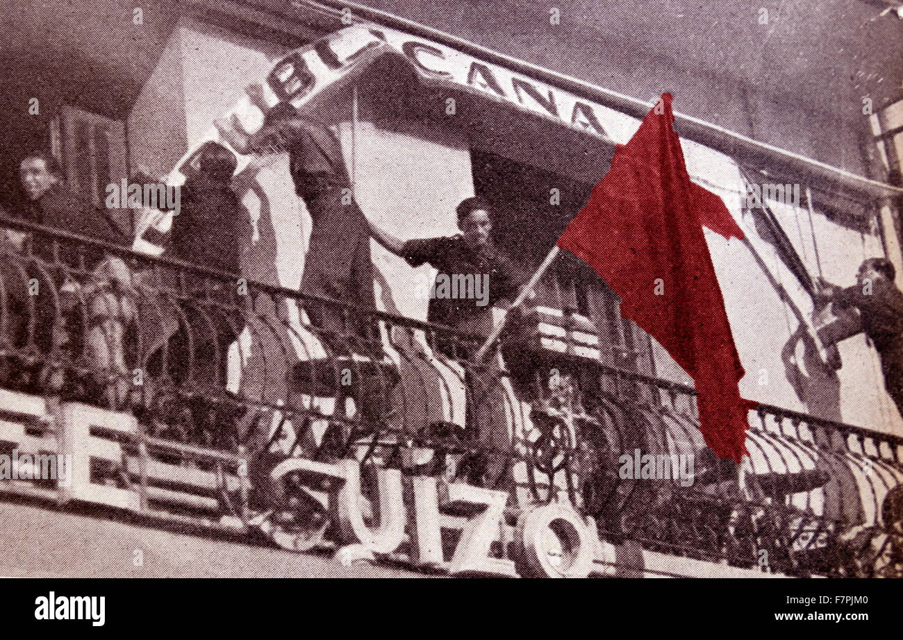 Communist flag is removed from a rebuplican building by falangist soldiers during the Spanish Civil War. Dated 1938 - Stock Image