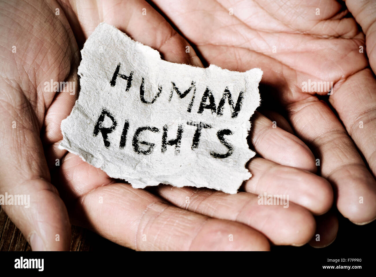 closeup of the hands of a young man with a piece of paper with the text human rights written in it, with a dramatic - Stock Image