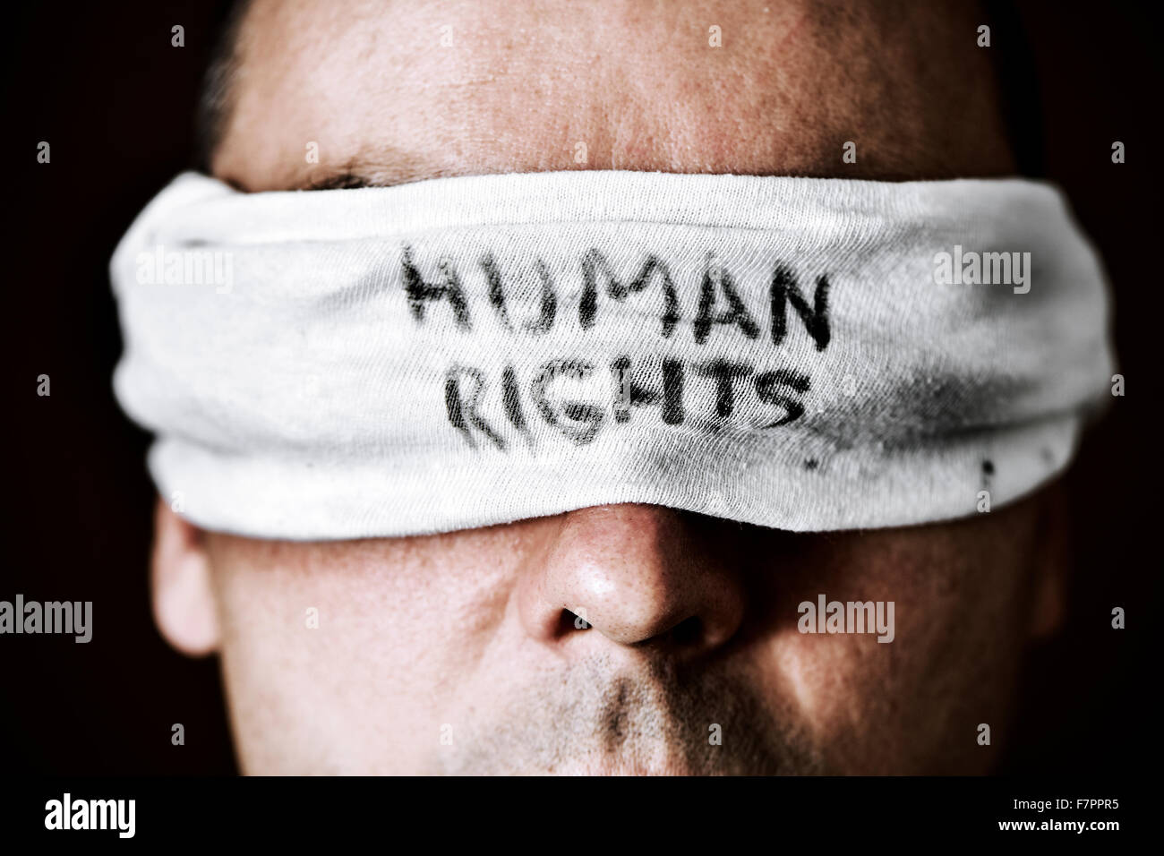 closeup of a young man with a blindfold in his eyes with the text human rights written in it, as a symbol of oppression - Stock Image