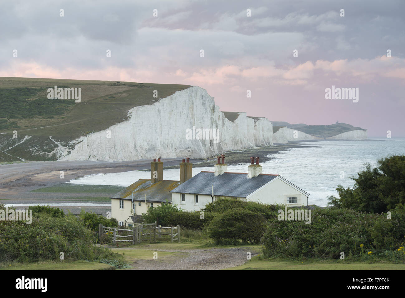 Stormy skies over the coastgard cottages at Cuckmere Valley, East Sussex, with the Seven Sisters seen beyond. - Stock Image