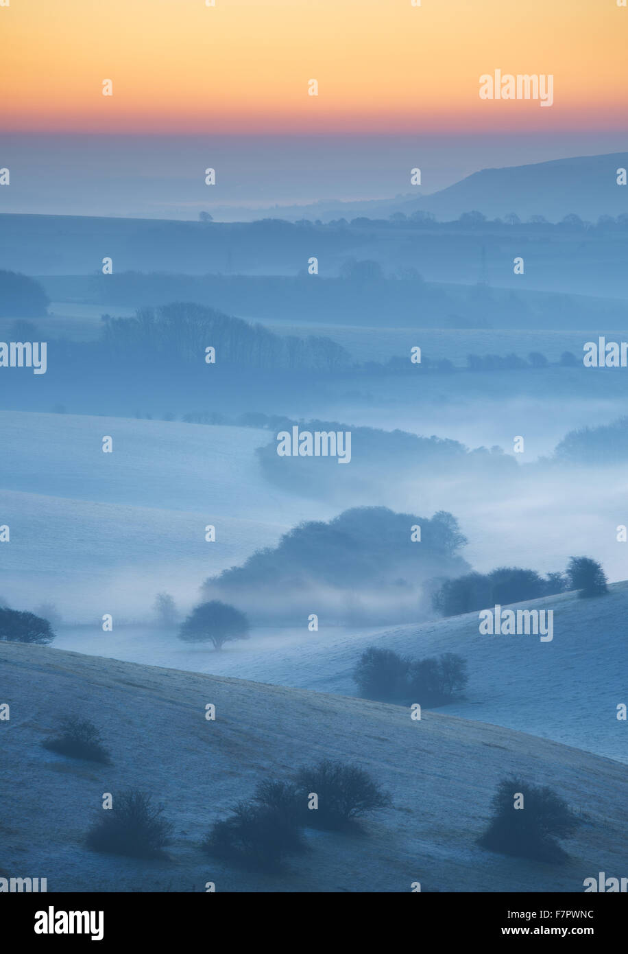 A misty view across the Sussex Downs at dawn, from Ditchling Beacon, East Sussex. - Stock Image