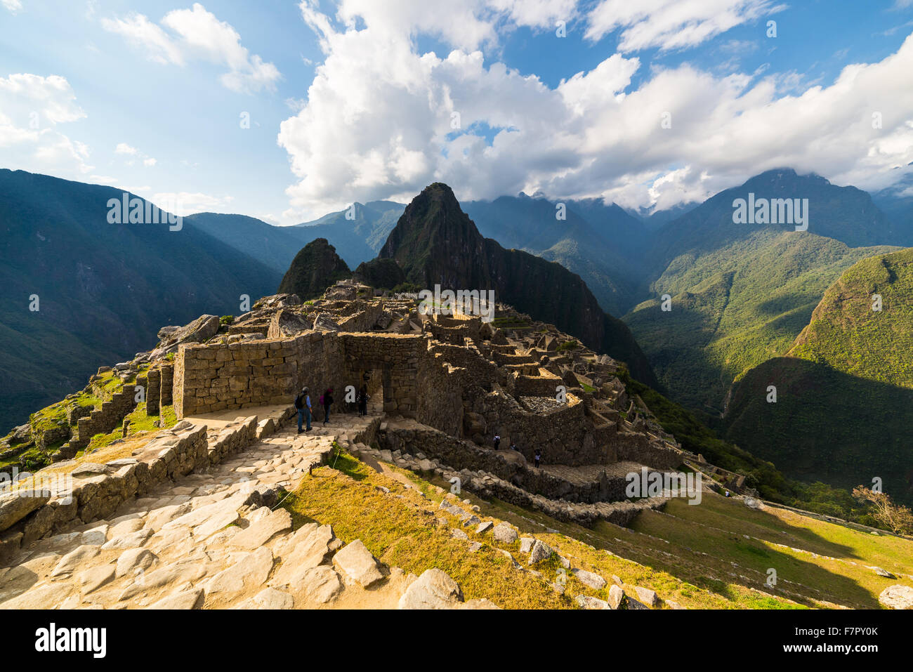 Machu Picchu partially illuminated by the last sunlight. Wide angle view from the terraces with scenic sky and glowing - Stock Image