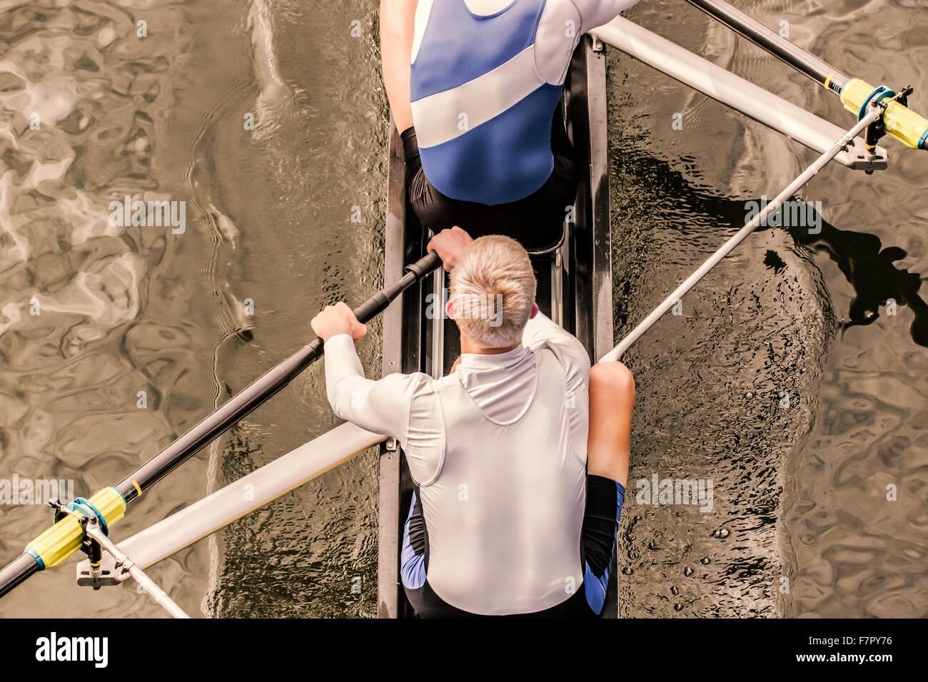 Top view of two athletic competition rower, who stroke their paddle through the water. - Stock Image
