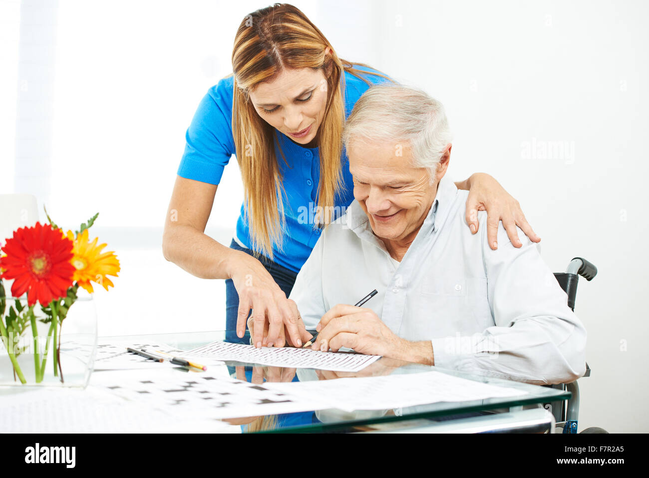 Senior man in wheelchair solving mazes as memory training with help of daughter - Stock Image