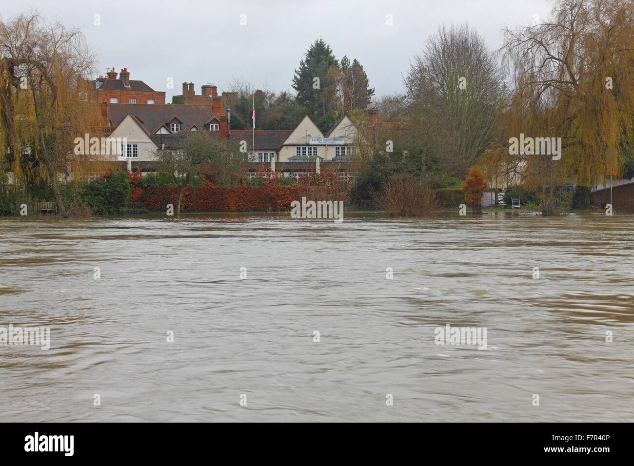 A view across a swollen river looking at a large hotel on the other side with flooded towpath and dark skies. - Stock Image