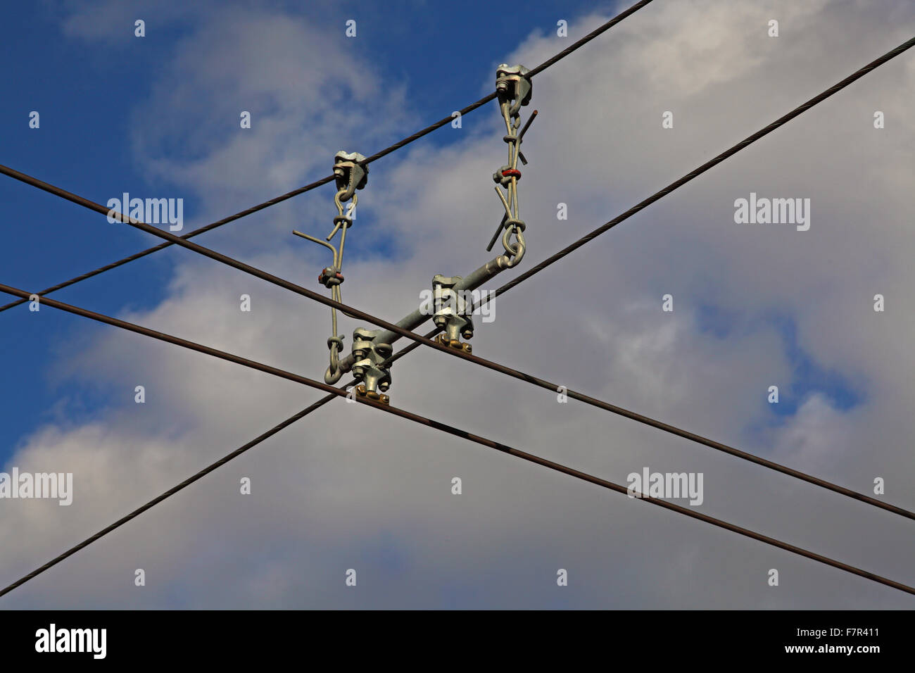 Overhead electric conductor wire with 'hangers' supporting the two main conductor wires and shows the fitting - Stock Image