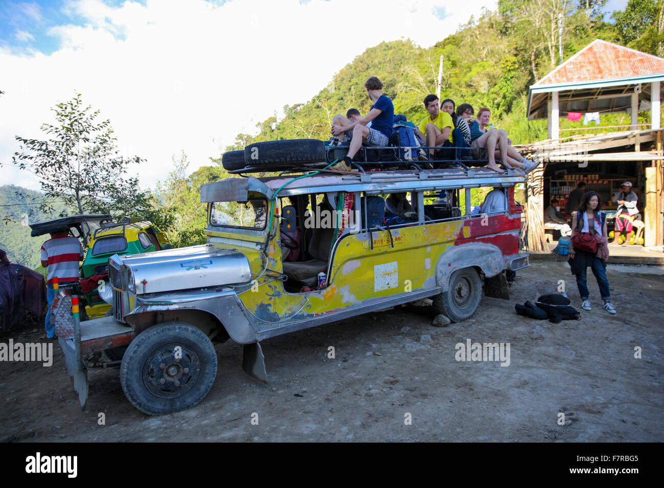Western backpackers on a rickety bus in Batad the mountains of Luzon, Philippines - Stock Image