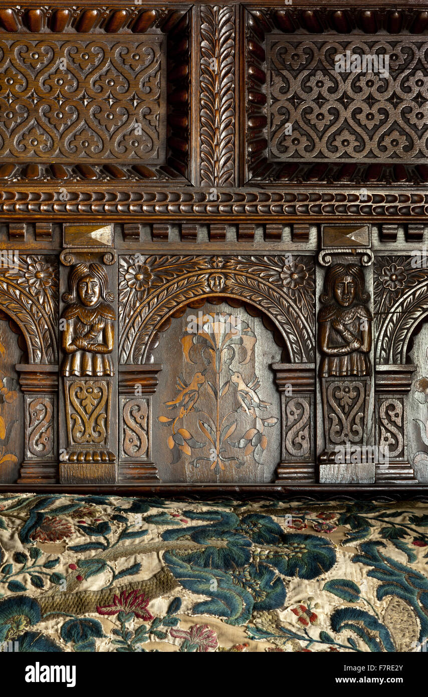 Detail of a carved bed head and bedspread in the oak bedroom at