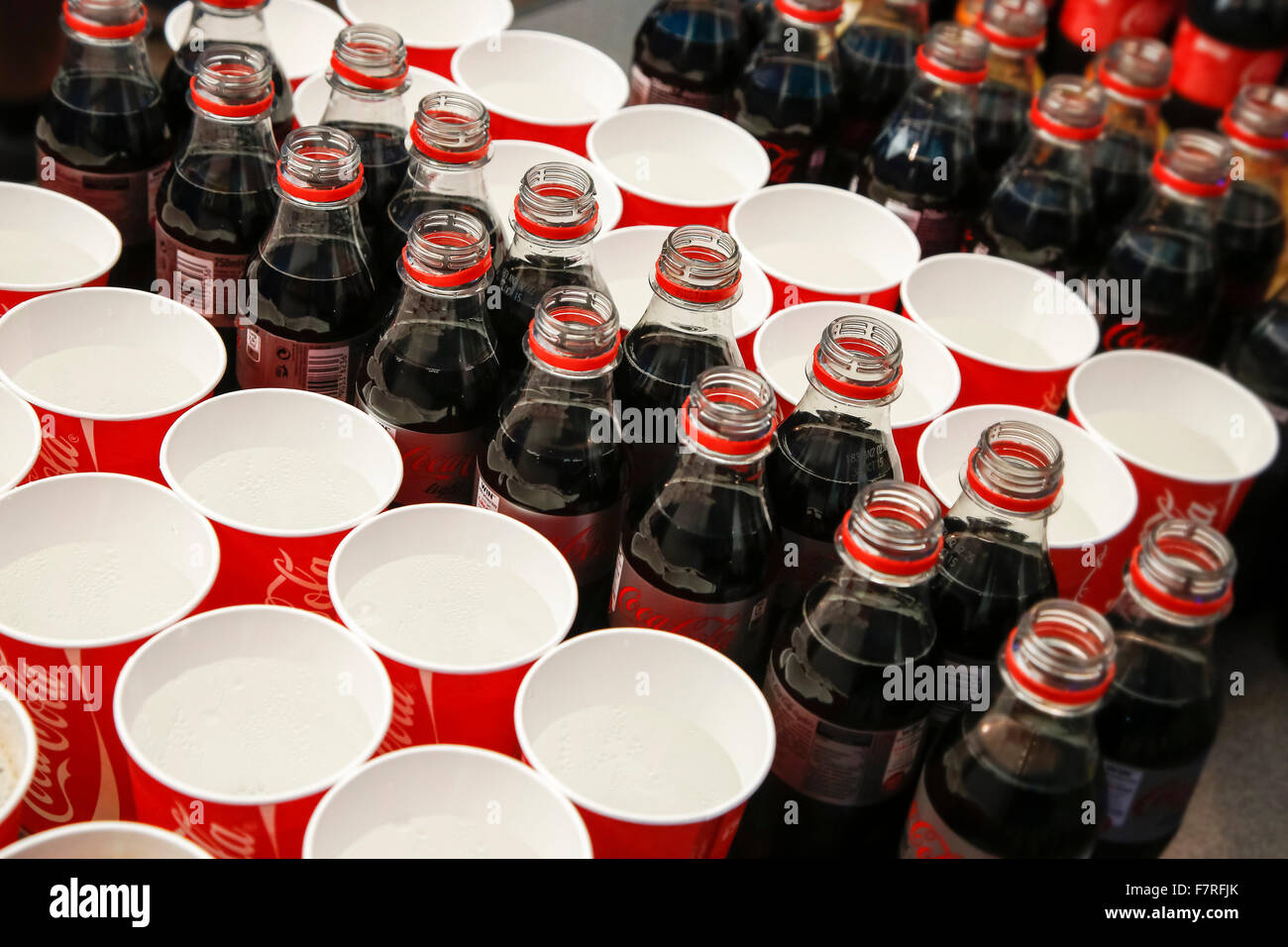 Open plastic Coca Cola bottles and throwaway cups with sparkling water at event - Stock Image