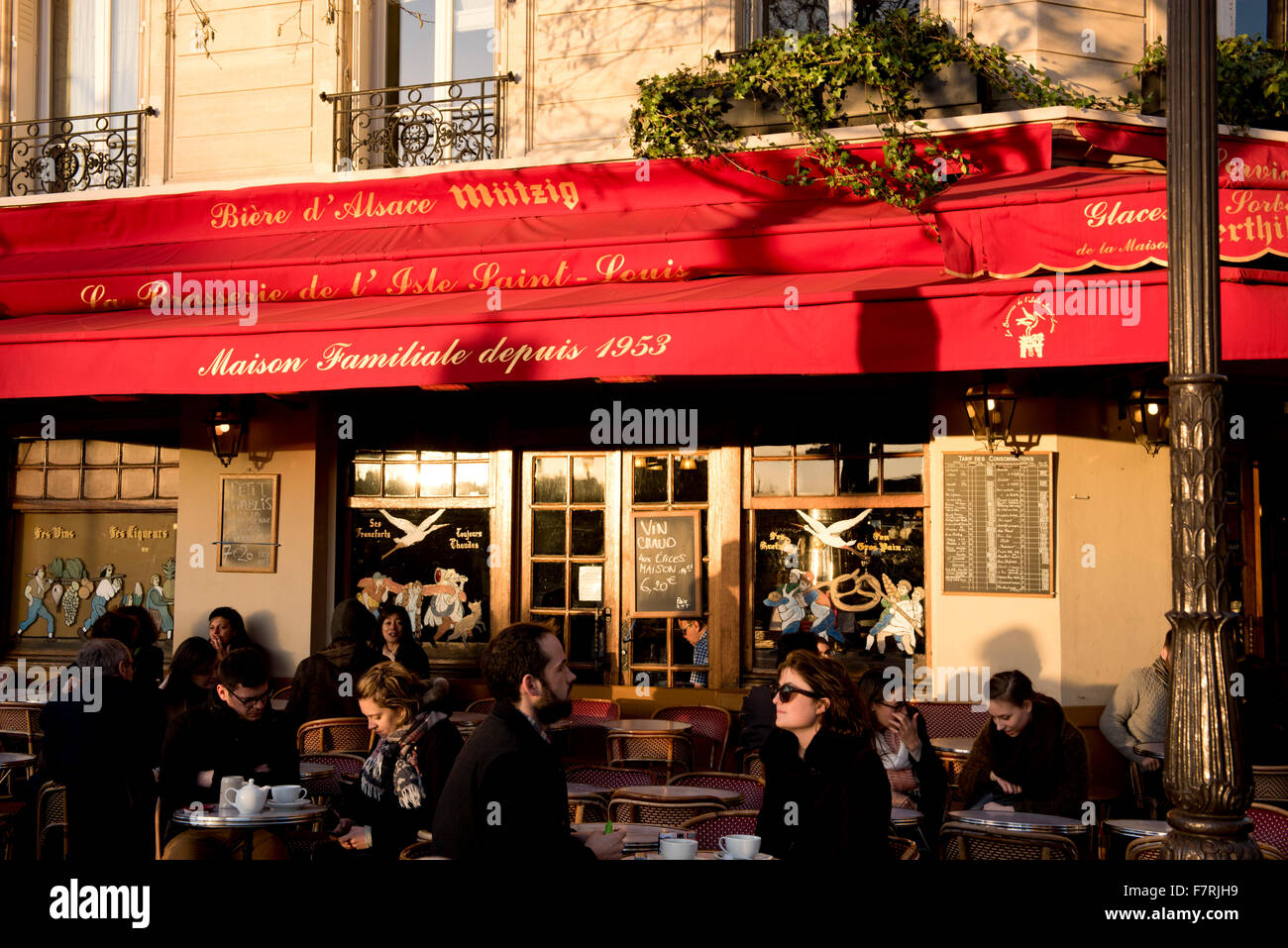 People sitting at pavement tables at a busy cafe on the Ile St Louis; Paris, France - Stock Image