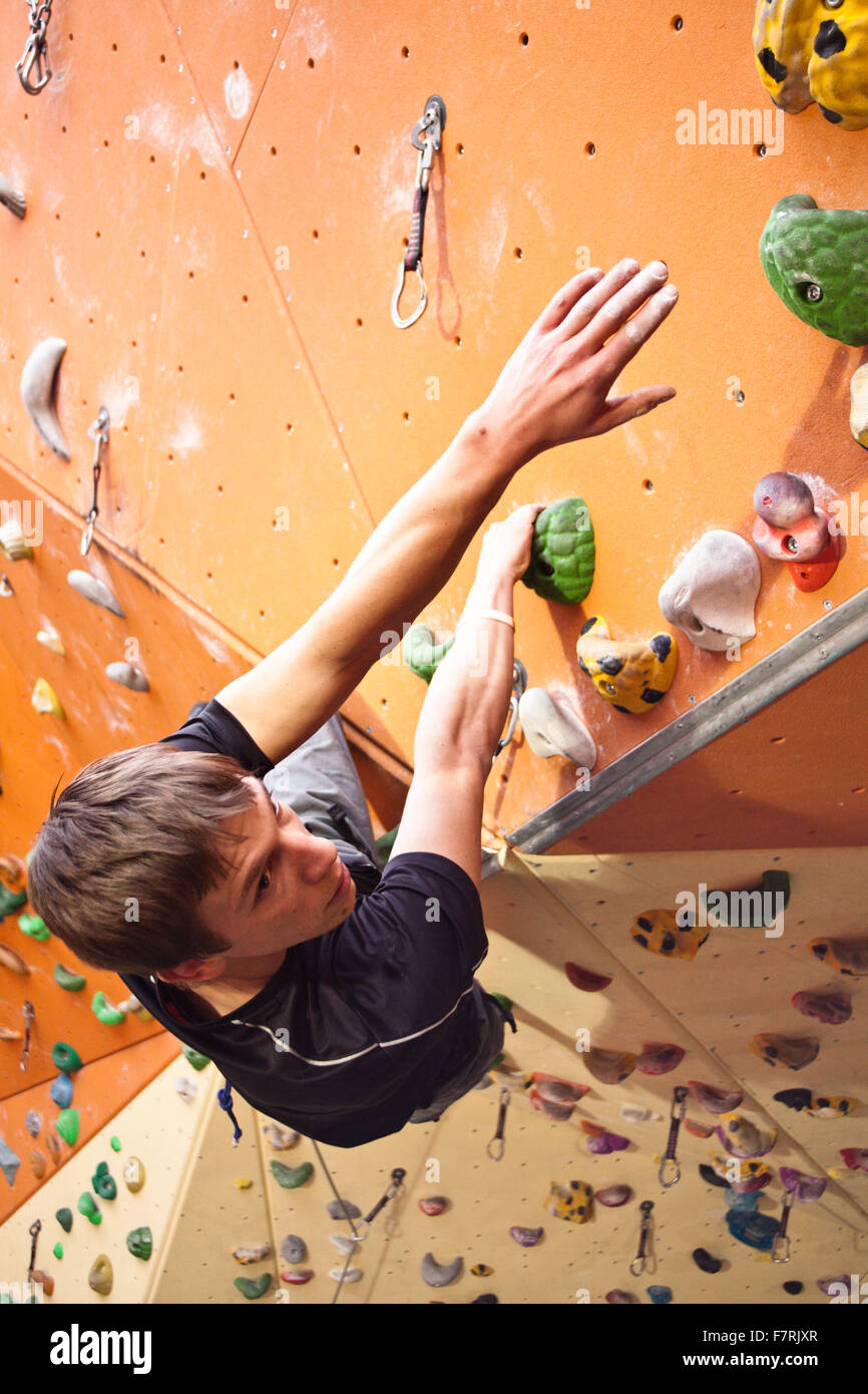 climber in an indoor climbing hall, about to reach the next hold - Stock Image