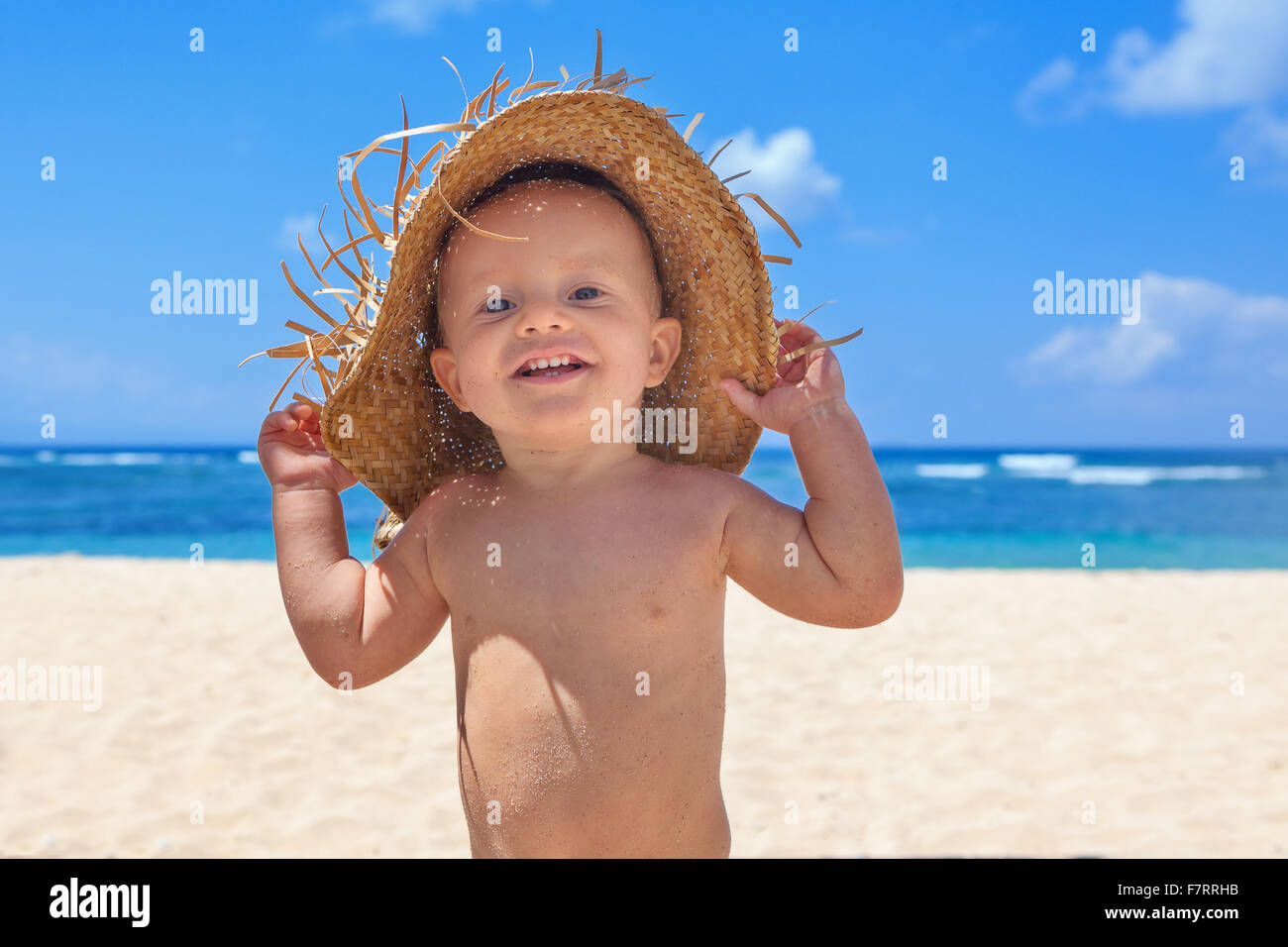 On sunny white sand beach muddy happy baby boy holds hat on head and has fun before swimming in sea waves. Stock Photo