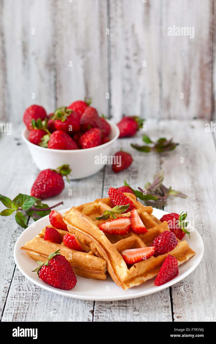 Belgium waffles with strawberries and mint on white plate. - Stock Image