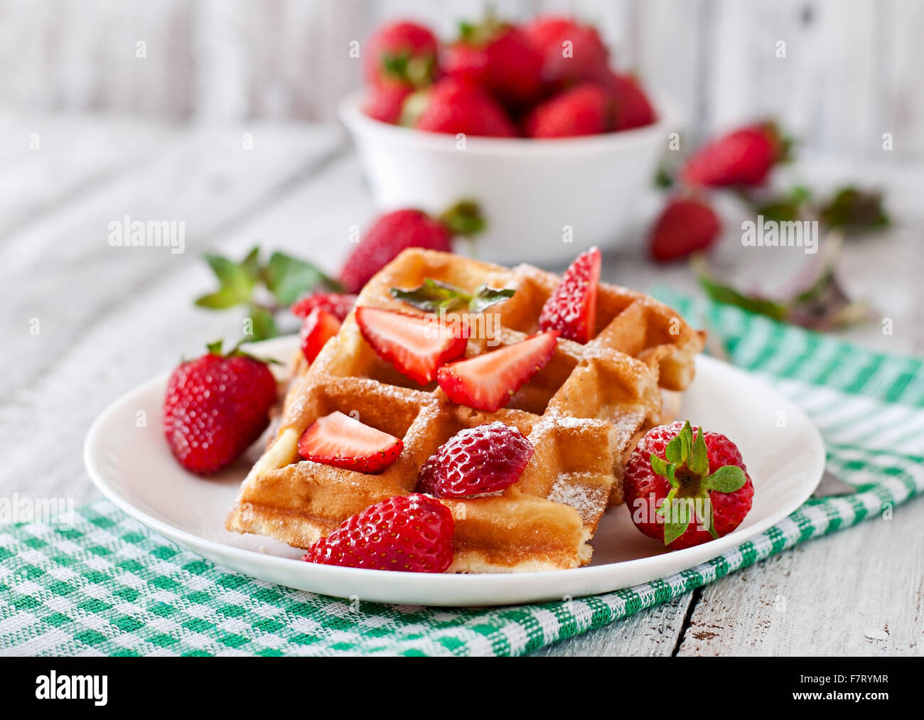 Belgium waffles with strawberries and mint on white plate - Stock Image